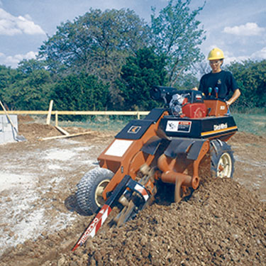 Orange trench digger with woman in yellow hard hat operating